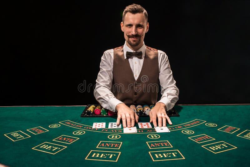 副主持人的画象在桌上拿着纸牌,赌博切削 黑色背景 免版税库存图片
