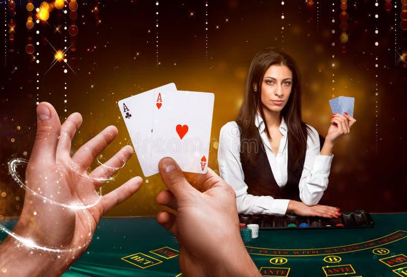 副主持人的画象拿着纸牌,赌博在桌上的芯片 黑背景 免版税库存照片