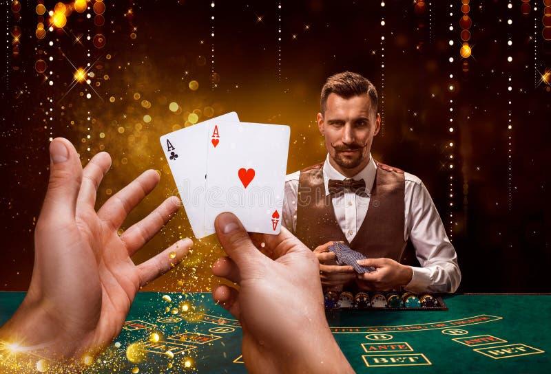 副主持人的画象拿着纸牌,赌博在桌上的芯片 黑背景 免版税库存图片