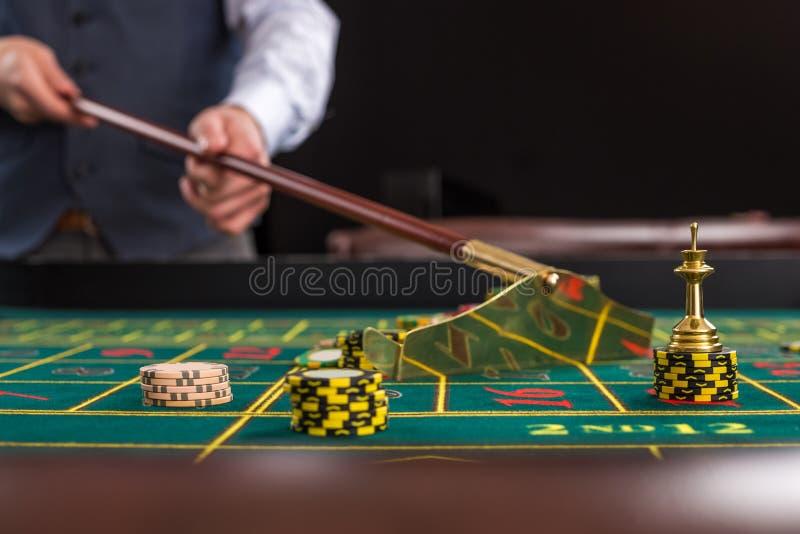 副主持人收集芯片使用棍子在赌博娱乐场 库存照片