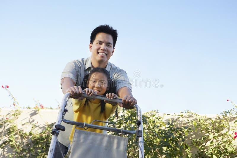 割草坪的父亲和女儿 免版税库存图片