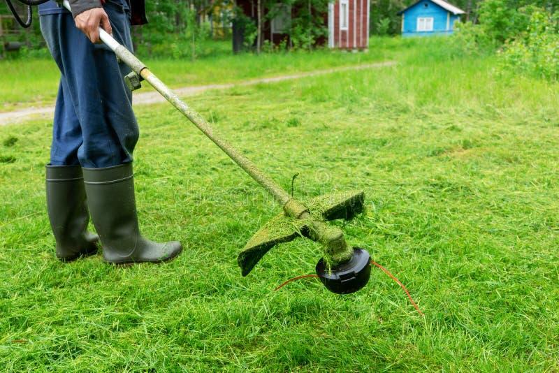 割草机 工作者,拿着割草机的一个人 园艺学工作 免版税库存图片
