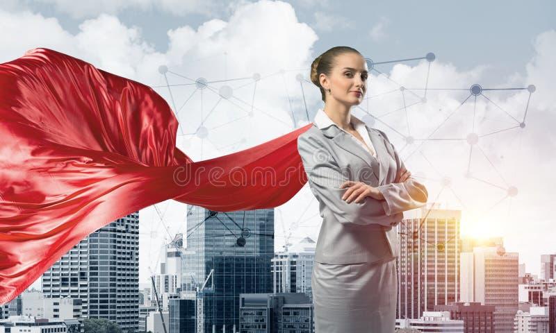 力量和成功的概念与女实业家超级英雄在大城市 库存图片