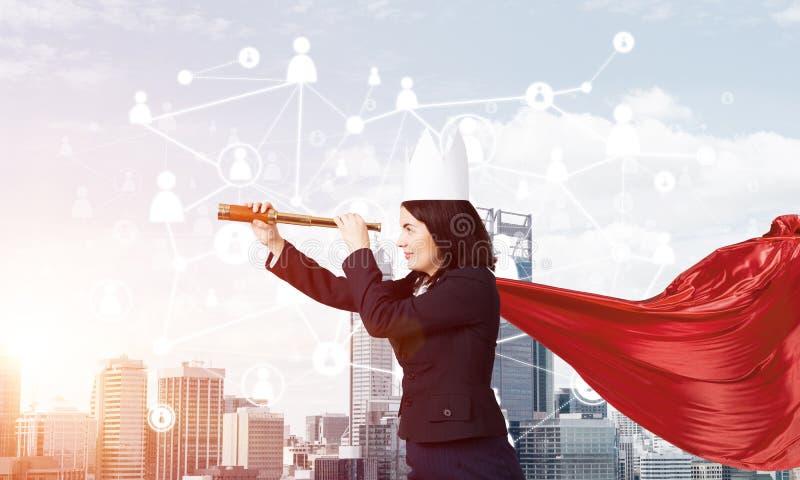 力量和成功的概念与女实业家超级英雄在大城市 免版税库存照片