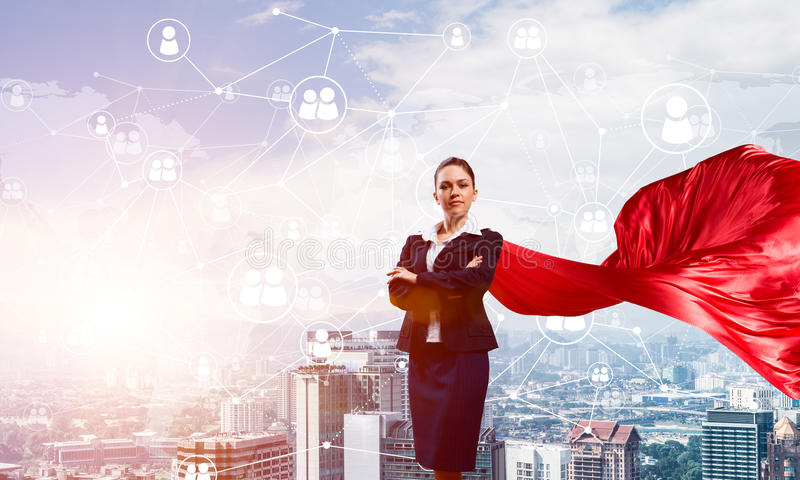 力量和成功的概念与女实业家超级英雄在大城市 库存照片