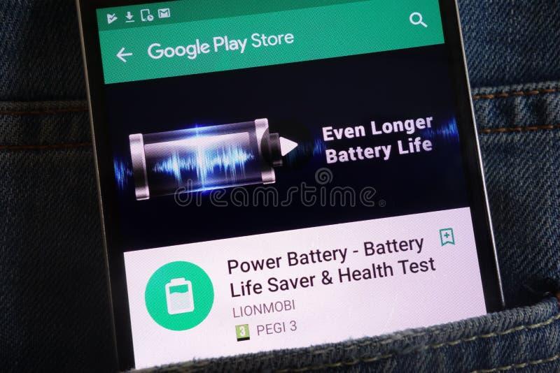 力量在谷歌戏剧在智能手机显示的商店网站上的电池应用程序掩藏在牛仔裤装在口袋里 免版税库存图片