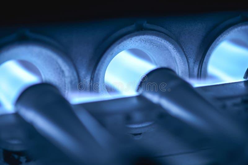 力量概念-燃烧器点燃与绯红色蓝色  库存图片