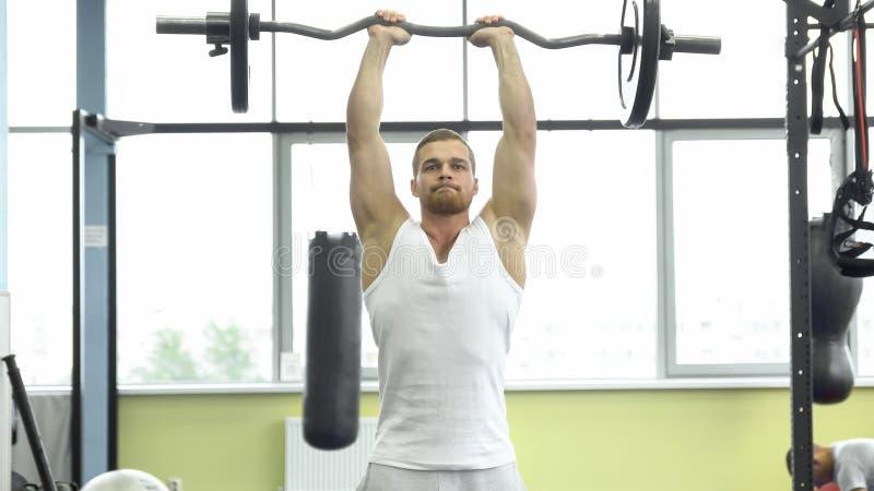 力量训练的肌肉人在健身房 运动员做与杠铃的三头肌锻炼 库存照片