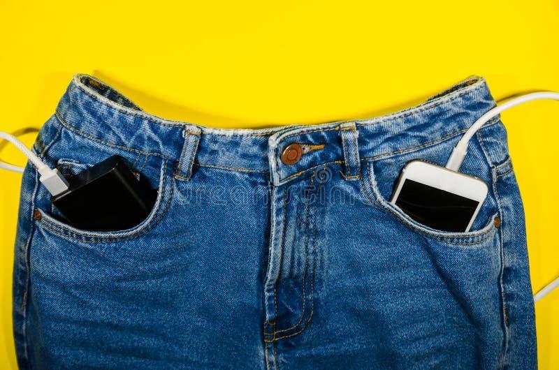 力量银行和一个电话在牛仔裤 免版税库存照片