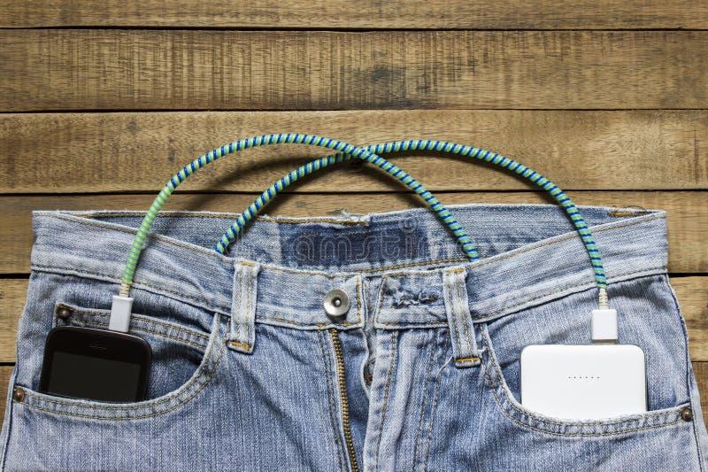 力量银行在牛仔裤的后面口袋在,在其他是暴民 图库摄影