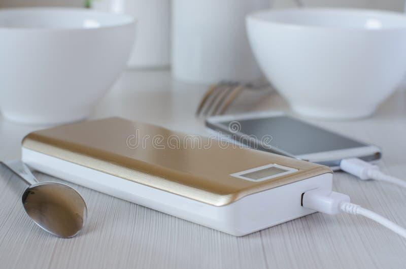力量银行收费在厨房用桌上的手机 免版税图库摄影