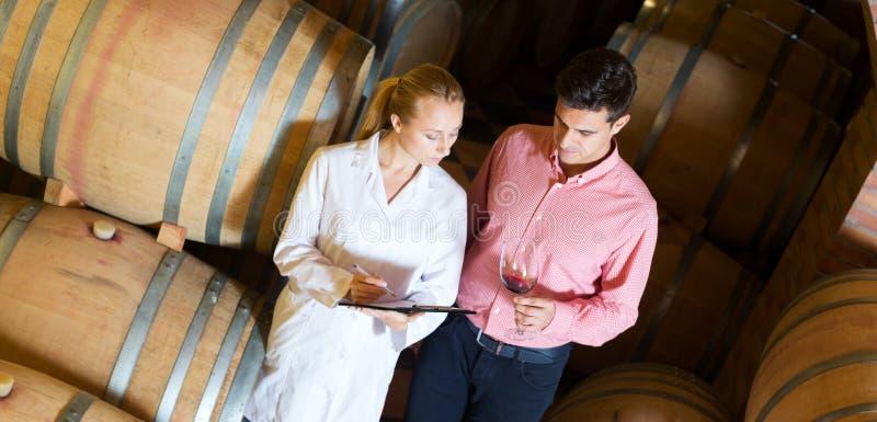 劝告的斟酒服务员男性顾客在酿酒厂地窖里 免版税图库摄影