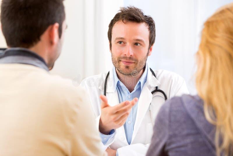 劝告年轻可爱的医生患者一对年轻夫妇  免版税库存照片