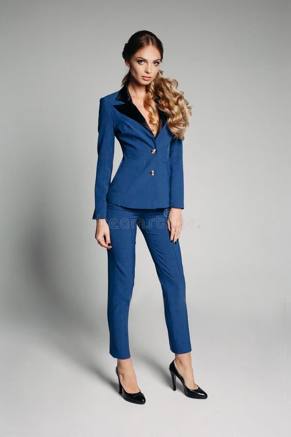 办公室严密的样式 有美妙地波浪发的白肤金发的女孩在一件蓝色,时髦的办公室夹克 妇女有尖叫 库存照片