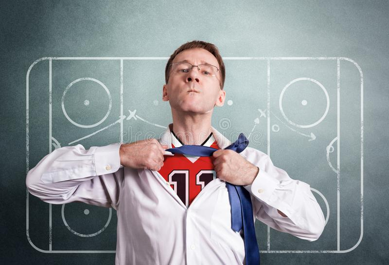办公室人打开一件白色衬衣并且显示曲棍球体育形式 在比赛的背景图画教练的计划 库存照片