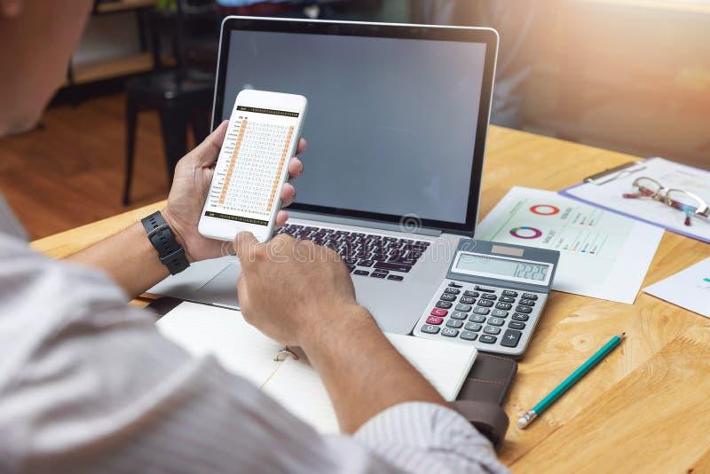 办公室使用智能手机的商人工作,配合的企业和财务概念和谈论投资经营计划  免版税库存照片