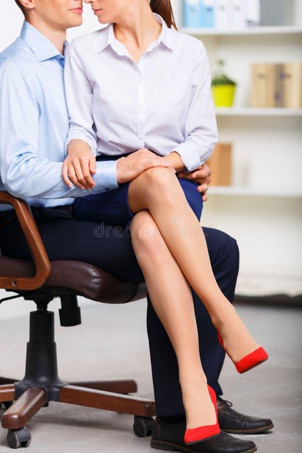 办公室助理坐工友膝部 图库摄影