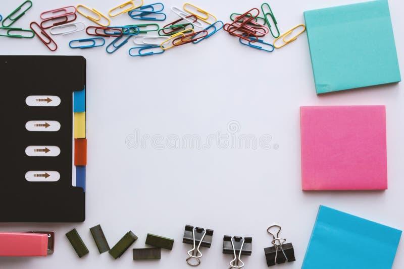 办公室固定式集合包括笔记本,纸夹、稠粘的笔记薄、黏合剂夹子、钉书针和订书机在白色背景 免版税图库摄影