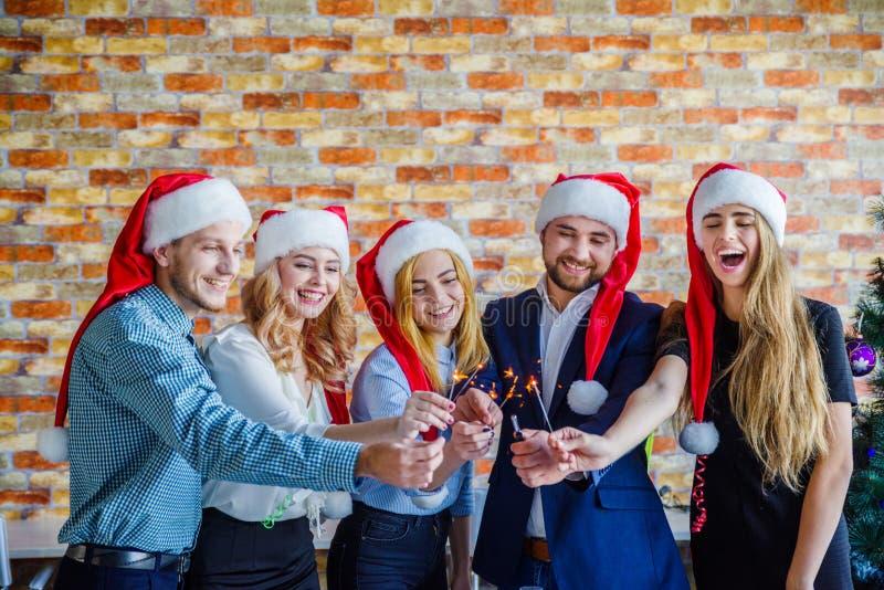 办公室圣诞晚会的企业同事 到达天空的企业概念金黄回归键所有权 免版税库存照片