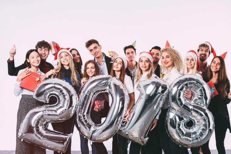 办公室圣诞晚会2018年 小组拿着银的圣诞老人帽子的快乐的青年人上色了数字气球 免版税库存照片