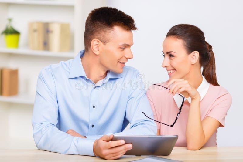 年轻办公室夫妇分享爱恋的神色 库存图片