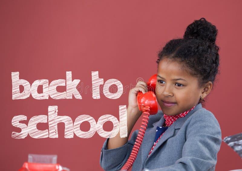办公室孩子女孩谈话在有回到学校课文的电话反对红色背景 库存图片