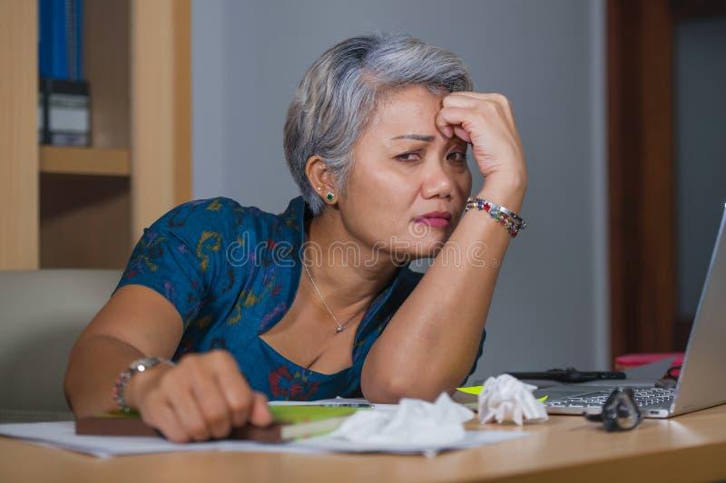 办公室工作在手提电脑书桌上的哀伤和沮丧的成熟可爱的亚裔妇女生活方式画象被注重和疲乏 库存照片