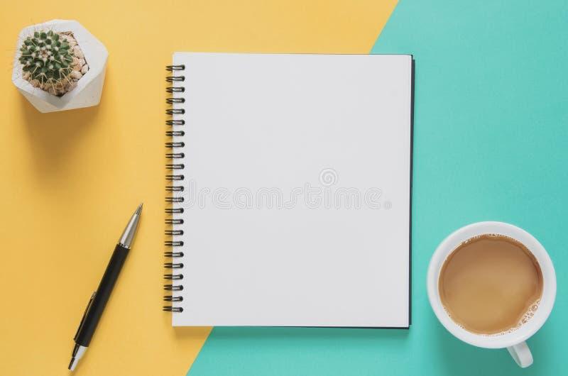 办公室工作场所最小的概念 有咖啡的空白的笔记本,仙人掌,在黄色和蓝色背景的铅笔 免版税库存照片