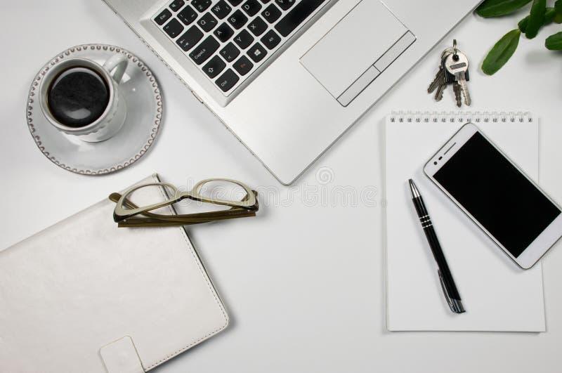 办公室工作场所顶视图有膝上型计算机的,笔记薄,钥匙,玻璃,电话,在白色书桌上 免版税库存图片