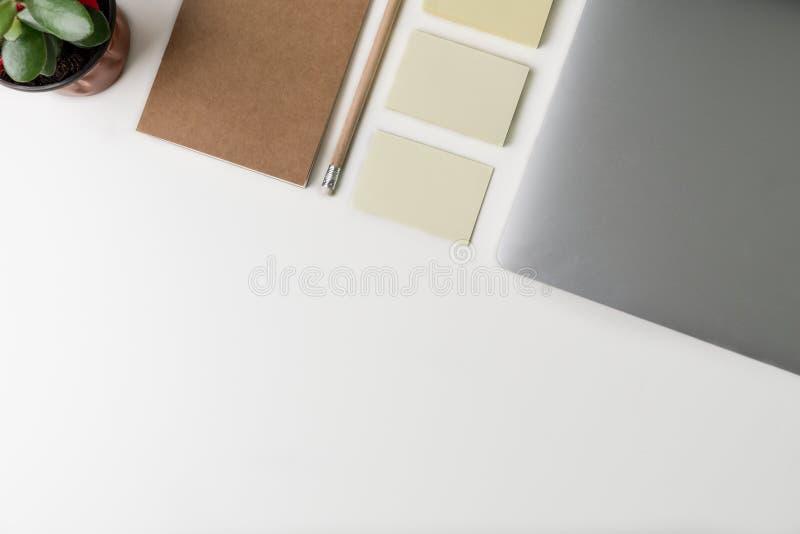 办公室工作场所顶视图  有拷贝空间的白色书桌 在桌上的平的位置视图与膝上型计算机,铅笔,笔记本,便笺 免版税库存照片