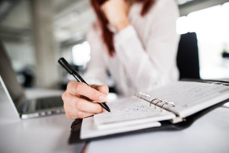 办公室工作的无法认出的女实业家 免版税库存图片