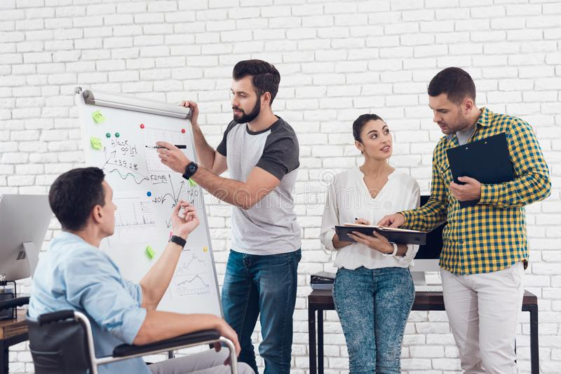 办公室工作者和人轮椅的谈论企业片刻在一个现代办公室 免版税库存图片
