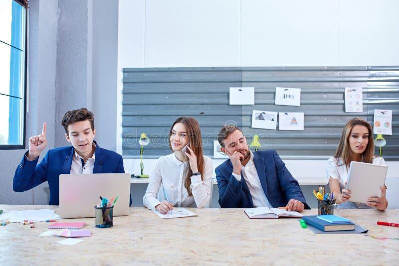 办公室工作者工作在膝上型计算机后的,片剂,谈话在睡着一的手机和那个 免版税库存图片