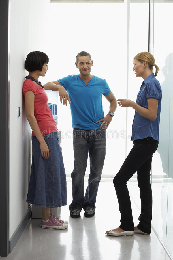 办公室工作者谈话由冷却器在走廊 免版税库存照片