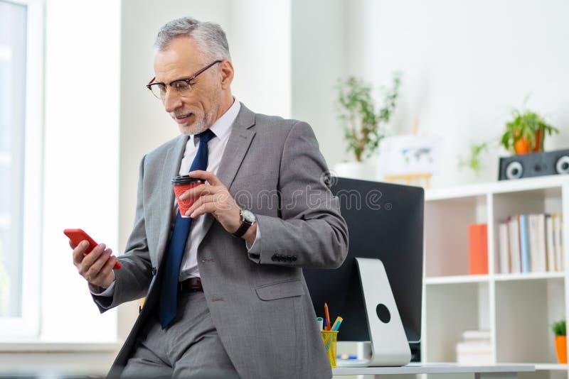 办公室成套装备的殷勤轻松的人喝新鲜的咖啡的 免版税库存图片