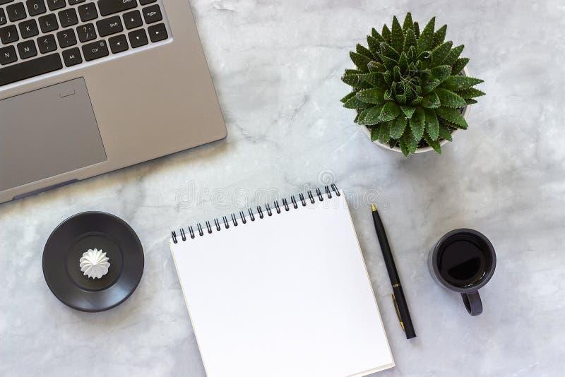 办公室或家庭桌书桌 灰色膝上型计算机,开放空的笔记薄,咖啡,多汁在时髦大理石背景的概念 库存图片