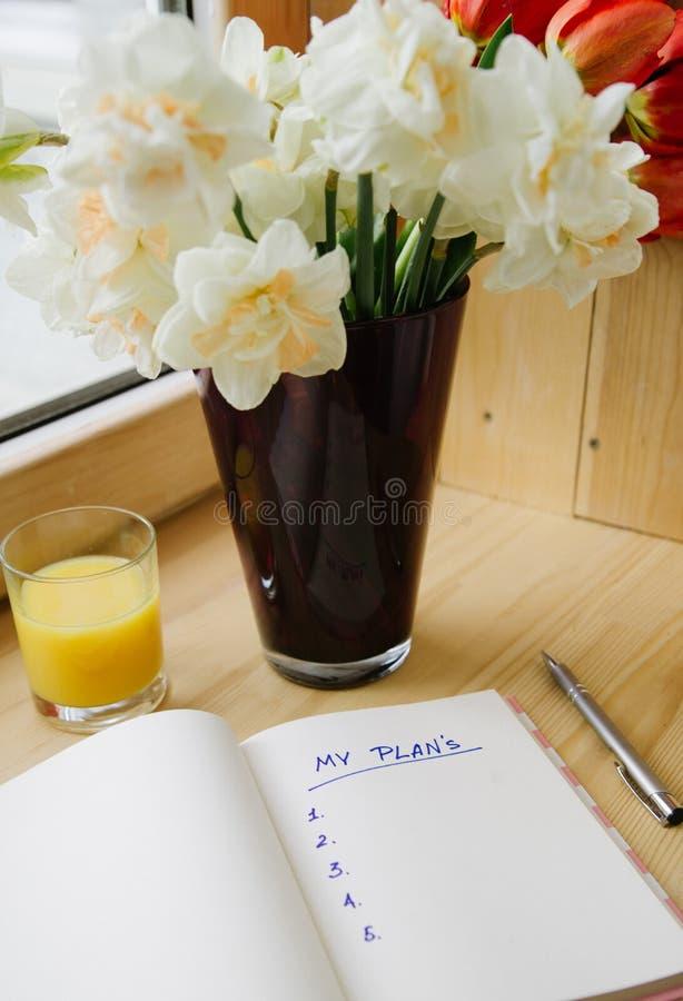 办公室文具,信封,在花瓶的花,在窗台的黄水仙顶视图  题字的地方 ? 图库摄影