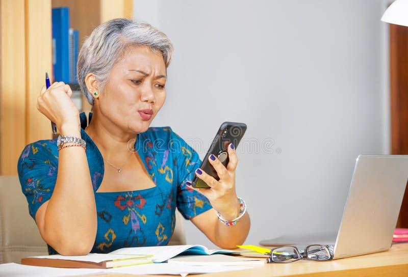 办公室有吸引力的担心和被注重的中部生活方式画象变老了亚裔妇女使用手机在手提电脑书桌 免版税库存图片