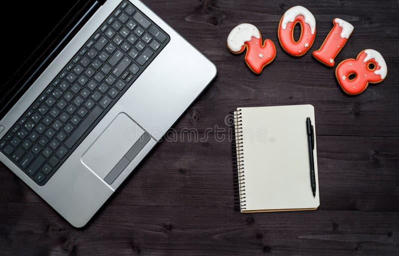 办公室有开放膝上型计算机的桌书桌顶视图,空白的笔记本和新年2018签署从姜饼曲奇饼的标志,复制空间 免版税库存照片