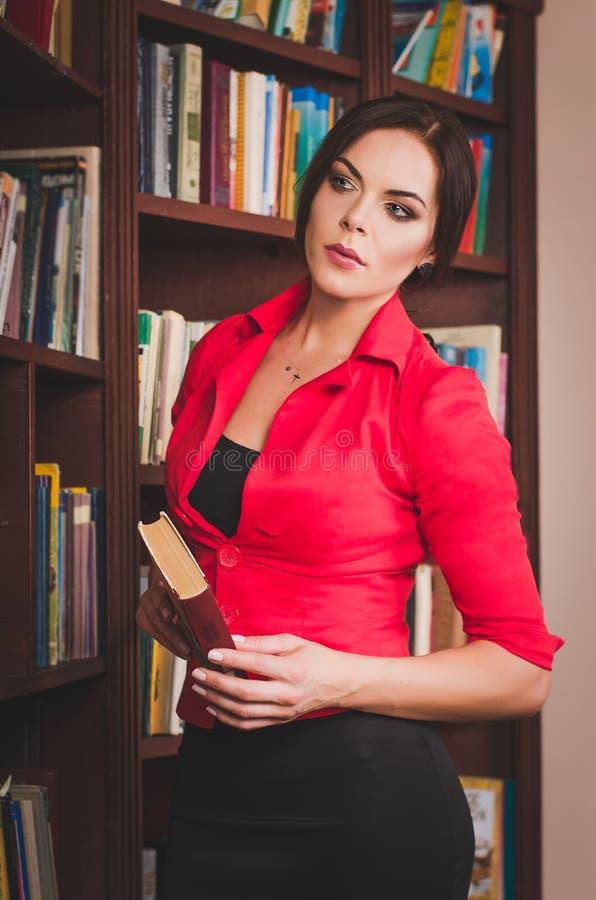 办公室服装常设nea的美丽的年轻棕色毛发的妇女 免版税库存照片