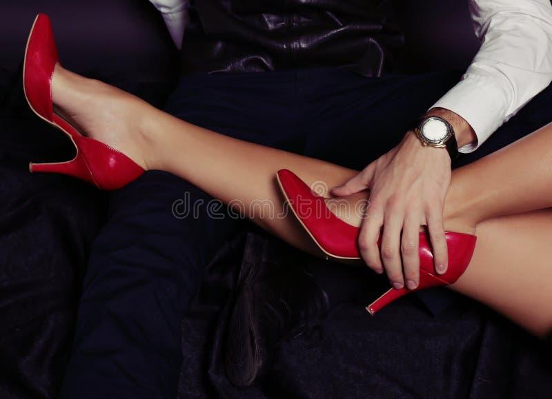 办公室爱情小说 在红色鞋子的妇女的腿 图库摄影