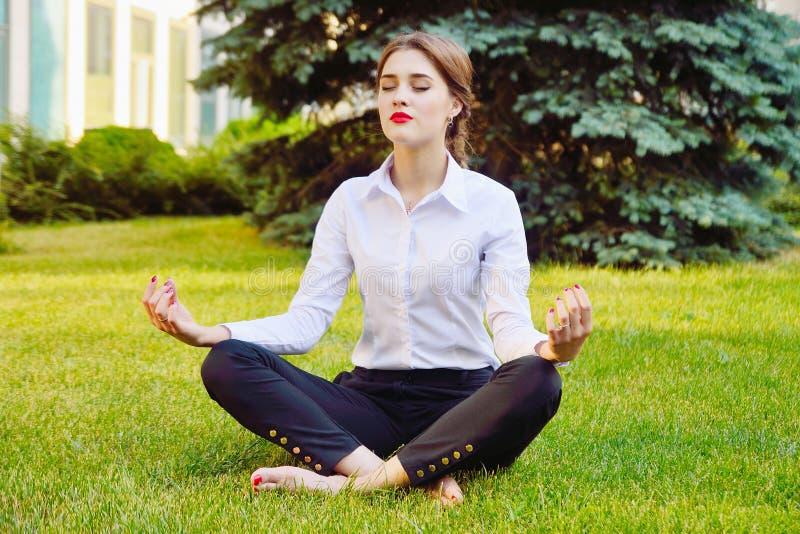 办公室瑜伽 莲花姿势的企业夫人坐绿草 再 免版税库存照片