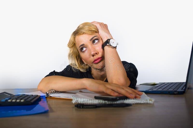办公室画象年轻哀伤和沮丧女商人工作懒惰在便携式计算机乏味和疲倦的书桌感觉看tho 免版税库存照片