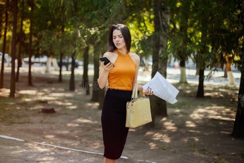 办公室经理妇女去工作,在电话的谈话和神色入本文 库存照片