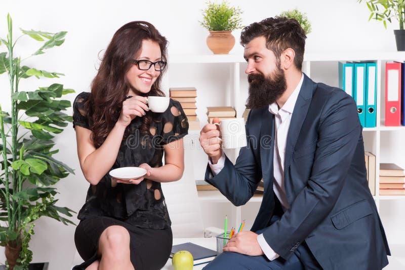 办公室谣言 夫妇工友放松咖啡休息 与与同事的份额咖啡 挥动的同事 r 免版税库存图片