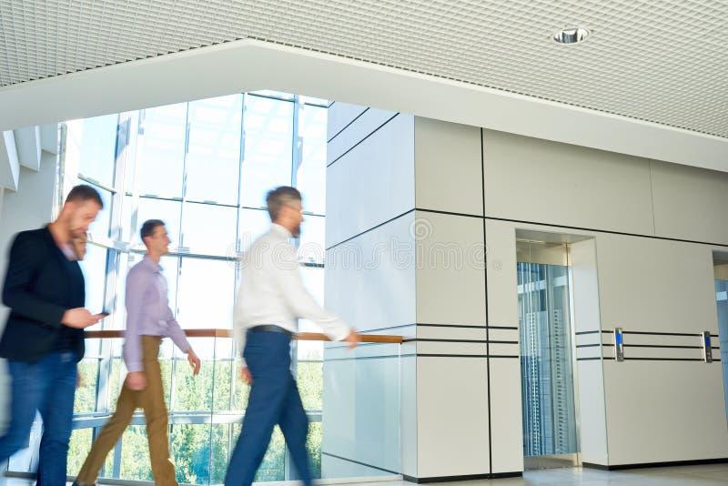 办公室走廊的男性同事 免版税库存照片