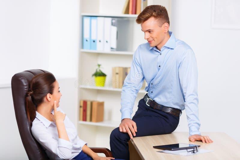 办公室辅助挥动与他的上司 免版税库存图片