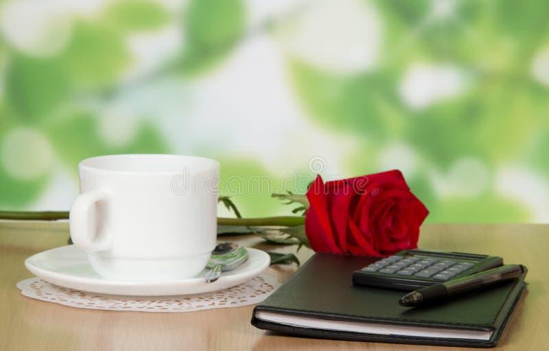 办公室辅助部件、杯子、茶碟和一朵玫瑰在桌上 免版税库存照片