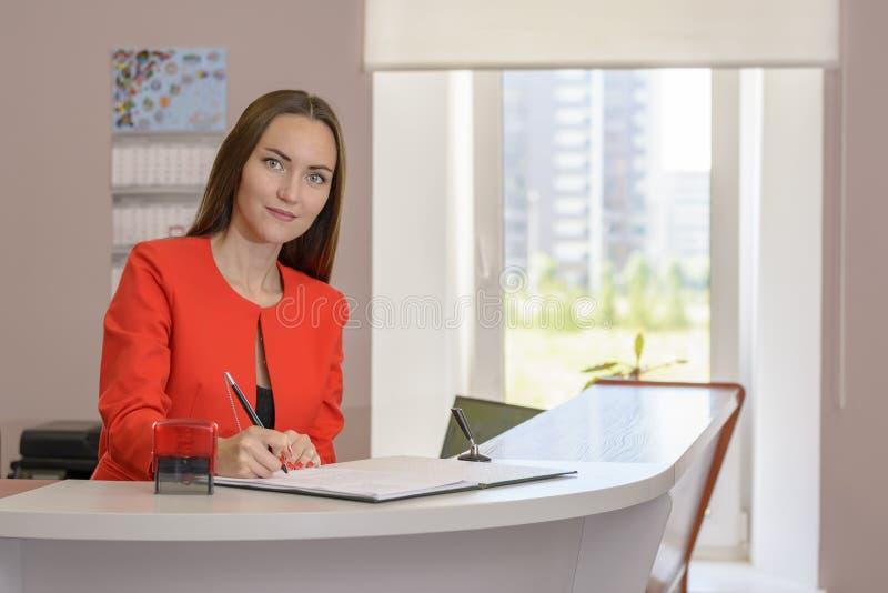办公室邮票的少妇秘书对文件 免版税库存照片