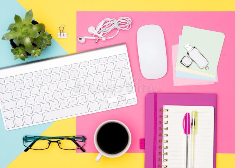 办公桌工作空间舱内甲板位置 工作区顶视图照片与键盘、笔记薄和咖啡的在淡色背景 免版税库存照片
